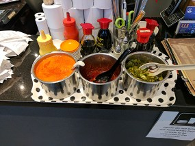 You can spike it and other dishes a bit with a trio of condiments from the cashier's desk.