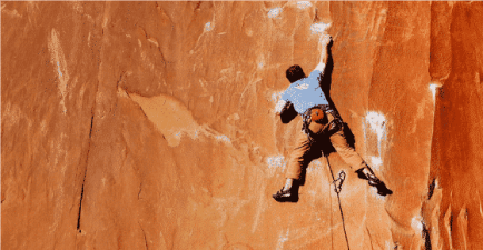 Man On Side Of A Red Rock Mountain Climbing Alone