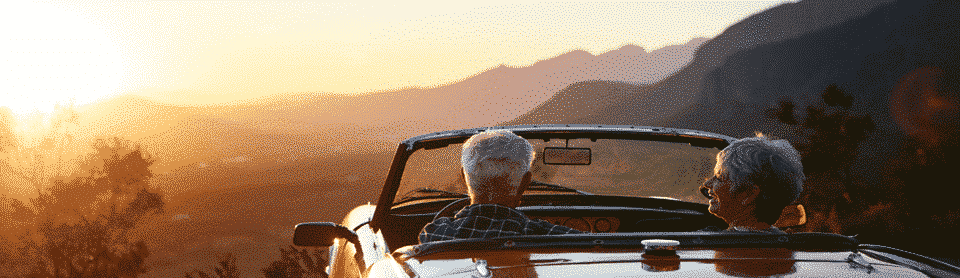 Retired couple looking at sunset in classic car