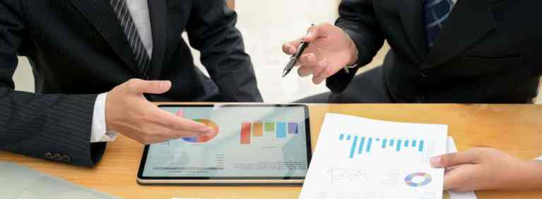 Business men analyzing financial charts on ipad long term care annuity page my annuity store, inc