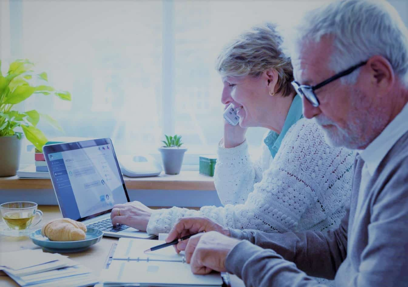 Senior Couple at Kitchen Table Completing Retirement Planning Checklist with laptop and pads of paper