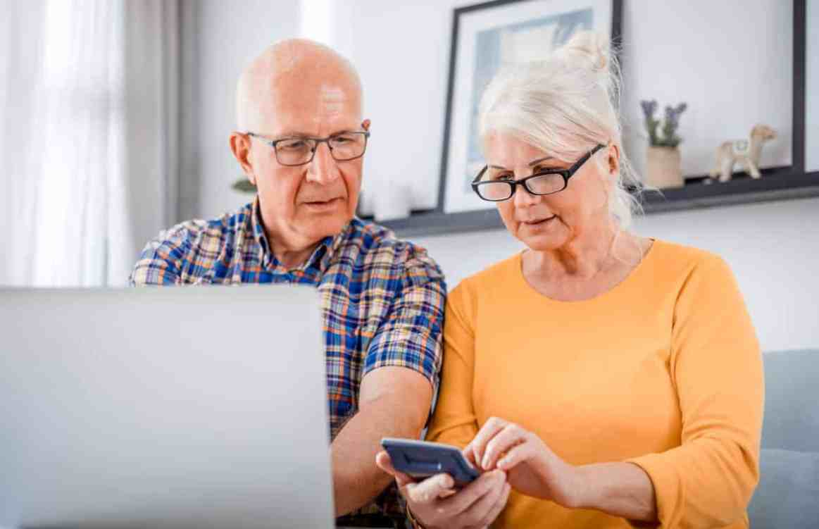 Worried older couple looking at laptop with calculator in hands - cd type annuity featured image