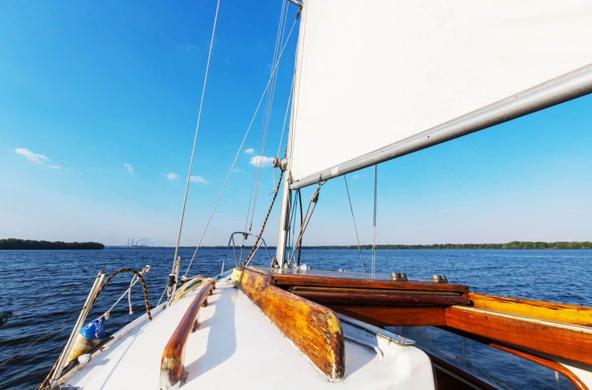 How Much Money Do I Need to Retire? Picture of white yacht on water with My Annuity Store, Inc. Logo on white sail.
