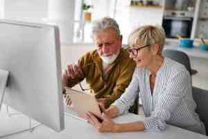 Immediate Annuity Payouts: Senior woman helping senior man to use computer