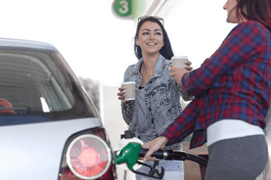 Two young ladies filling up car at gas station