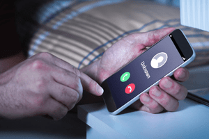 man holding smartphone screen displaying unknown caller