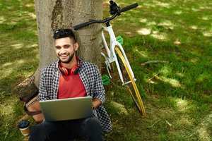 Young man sitting next to bicycle and leaning against tree while studying on laptop in park