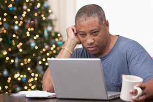 Middle-aged African American man with coffee looking up articles on laptop