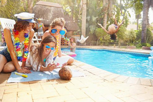 Three young ladies make plans by a pool in a tropical location
