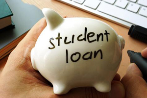 "Hand holding a small, white, porcelain piggy bank with ""student loan"" handwritten on the side."