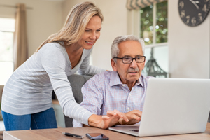 daughter helping elderly father check his account online
