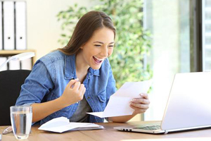 Young woman very happy about a paper statment that she is reading in her dining room in front of her laptop.