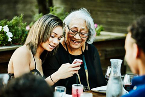 collefge age girl shares a meme on her phone with her grandmother while they have lunch at a cafe