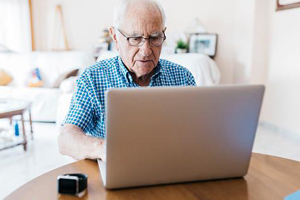 Older man looking concerned as he browses files on his laptop