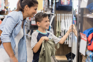 Mom and young boy shopping for school clothes at a department store