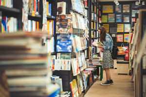 Young woman searches through shelves of books in a large bookstore or library