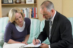 Insurance salesman signing insurance paperwork with a middle-aged lady