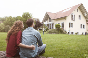 A young couple sits on the lawn of their modest home watching their two young children play in the yard