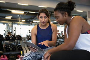 Personal trainer in a gym reviews the exercise & diet with her client