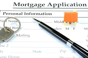 Close-up of a mortgage application on a desk with a pen and keys on top of the application