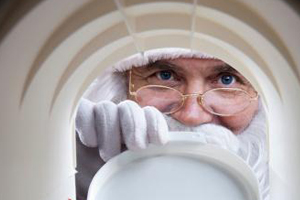 Close-up of Santa's face and glove as he peeks into the mailbox that you are in.