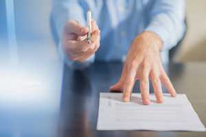 Business person handing pen over for viewer to sign