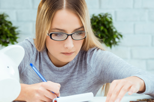 Young blond woman in glasses checks books and takes notes