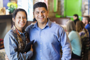 Hispanic couple in dining room of their family owned restaurant