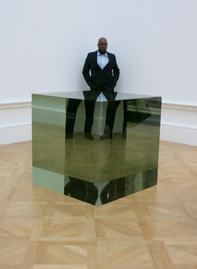 I love how the bored security man's legs are made to look by the perspex cube