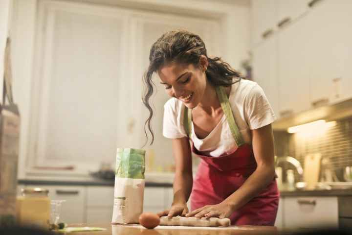 happy woman with rolling pin cooking at home