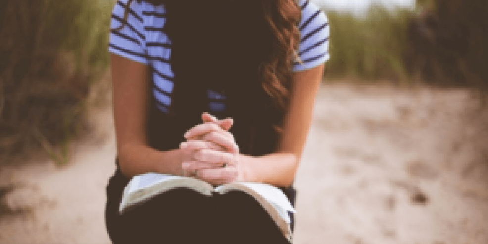 girl with praying hands on top of Bible