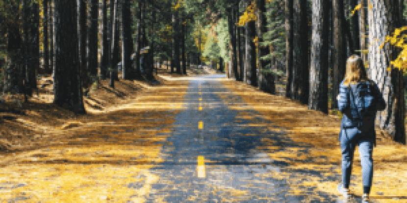 Girl walking on side of empty road