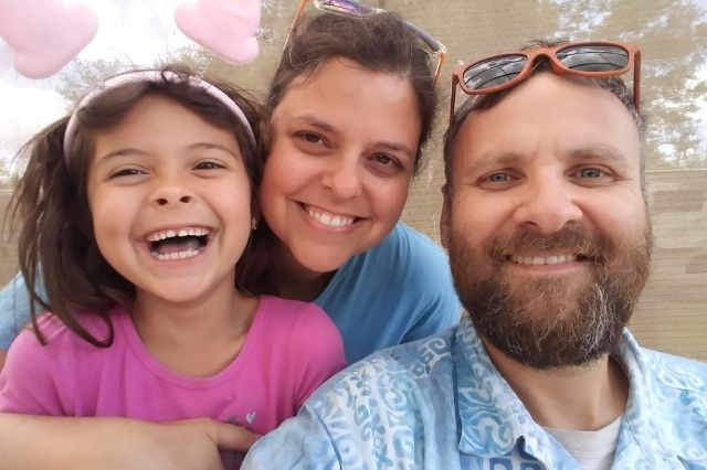 Picture of young brunette girl in pink shirt, a mom with a blue shirt, and a dad in a blue plaid shirt