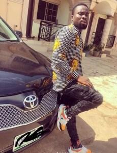 Obotuke Timothy Sirbalo standing beside a car