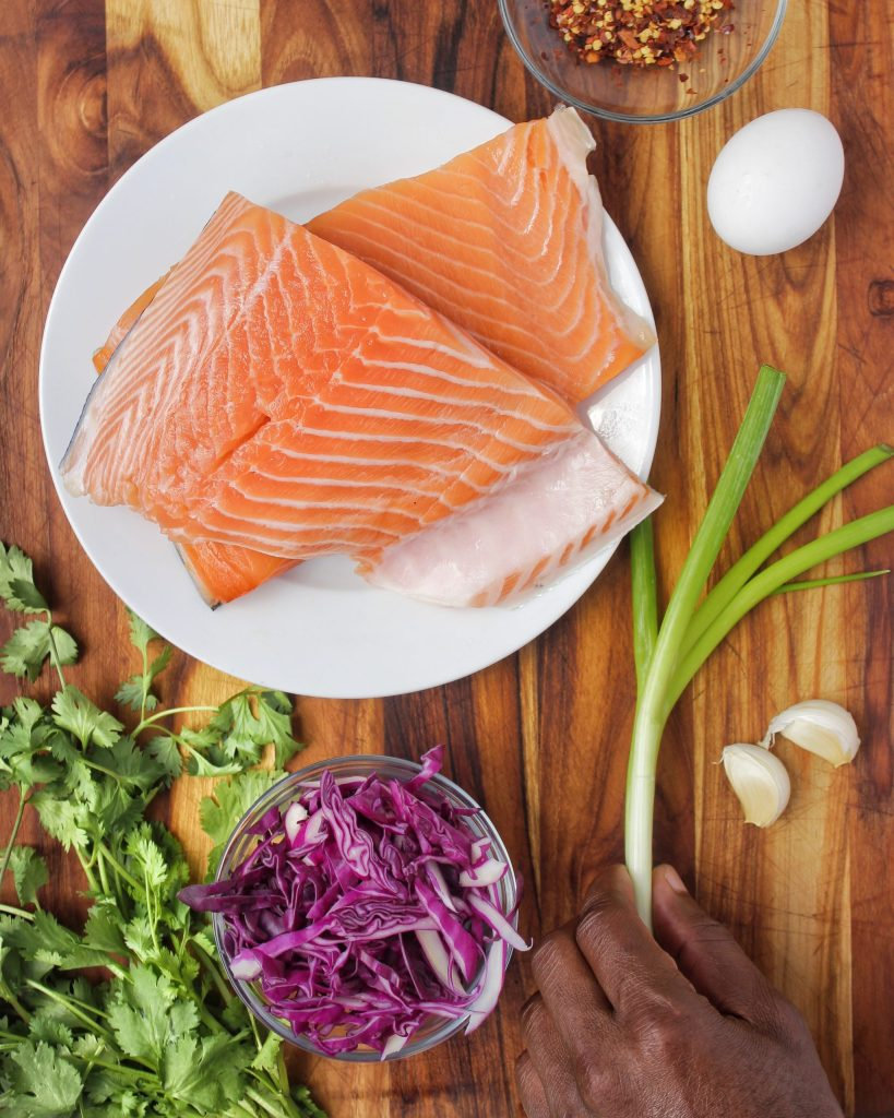 Ingredients for Spicy Sesame Salmon Burger topped with cucumber, spicy mayo and red cabbage