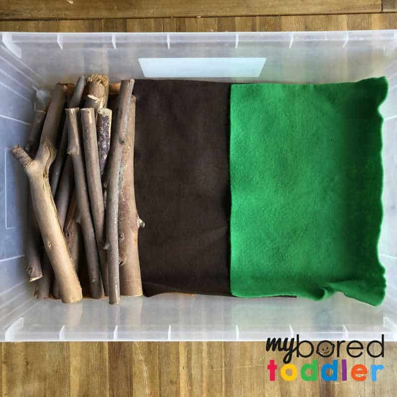 setting up a sensory wood pile small world play for toddlers 2