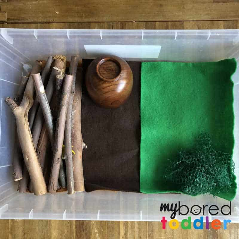 setting up for a sensory wood pile small world play for toddlers 3