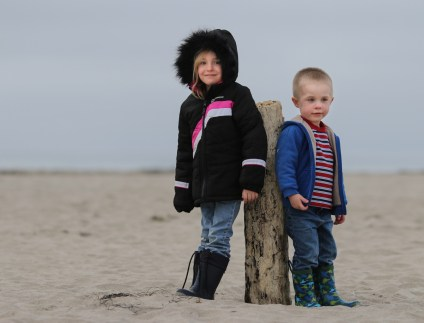 two kids leaning on a post at the beach