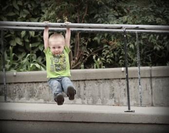 little kid hanging on railing