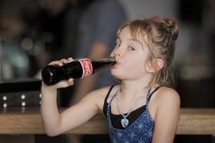 smiling girl drinking bottle of coke