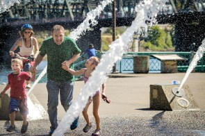 dad and kids running through fountain