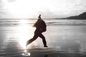 lady jumping on the beach in the sunlight