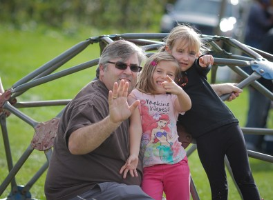 dad and two little girls waving