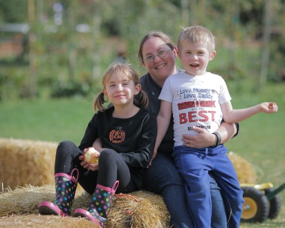 Mom with two kids at apple tree farm