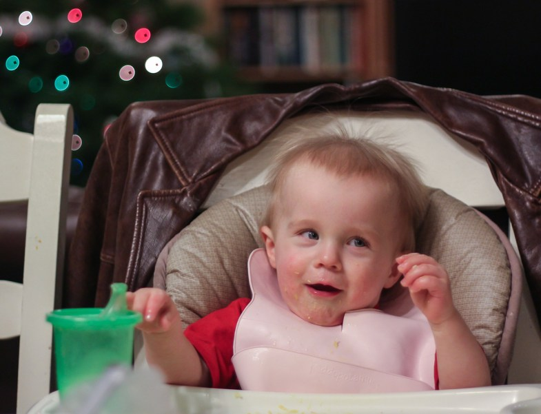 little boy with funny expression in high chair