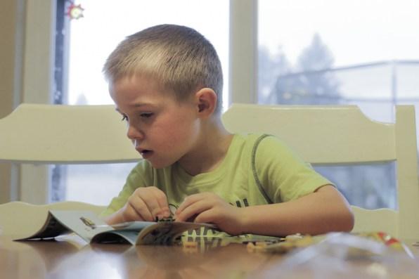 little boy building Lego set