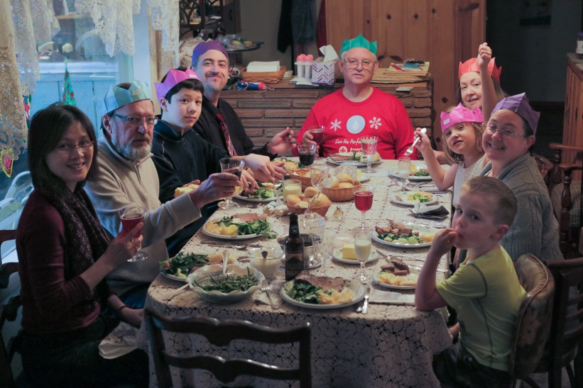 family wearing goofy hats at Christmas table