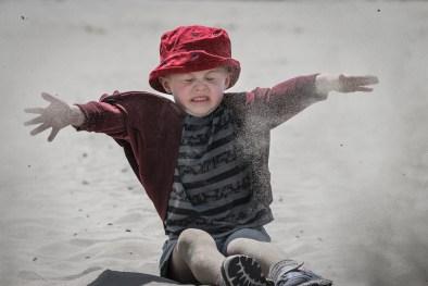 little boy throwing sand on beach
