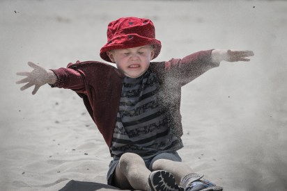 little boy throwing sand on beach