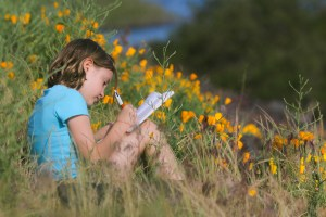 little girl sitting in field of flowers writing in journal